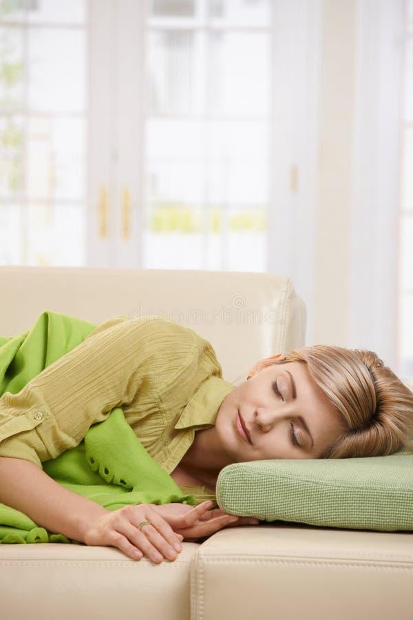 Белокурая женщина спать на кресле стоковые изображения rf