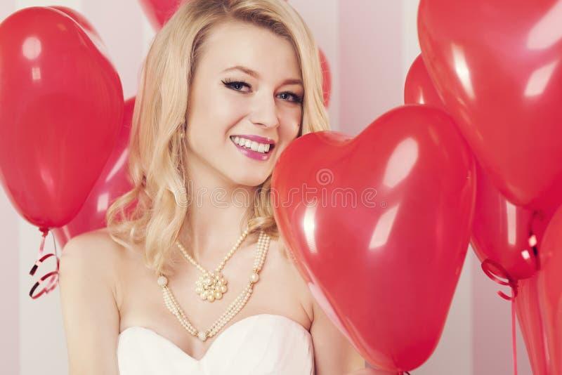 Белокурая женщина стоя вокруг воздушных шаров стоковые изображения