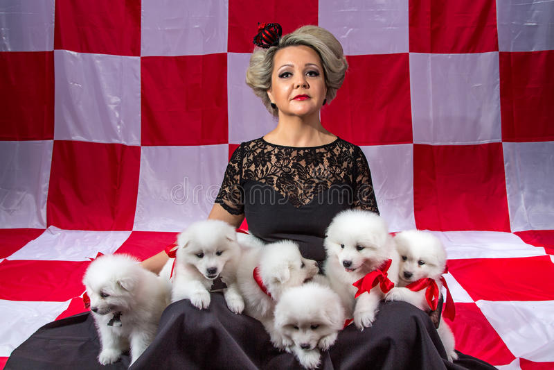 Белокурая женщина с белыми щенятами стоковое фото rf