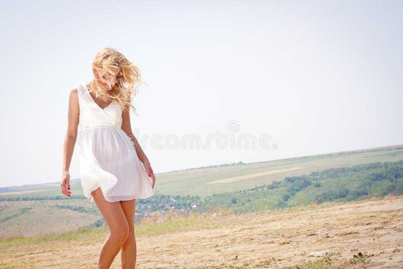 Белокурая женщина с волосами и sundress быть дунутым ветром стоковое изображение rf