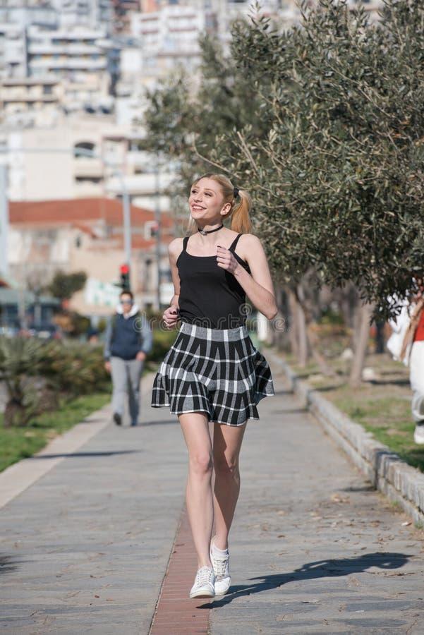 Белокурая женщина с маленькими отрезками провода бежит на городском пейзаже тротуара на предпосылке стоковое фото
