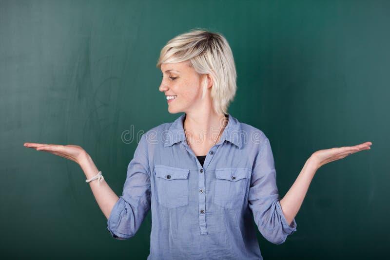 Белокурая женщина с пустыми ладонями против доски стоковое изображение rf