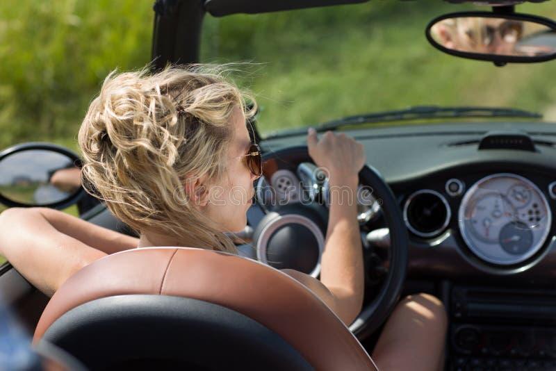 Белокурая женщина управляет автомобилем cabrio, в солнечности лета стоковая фотография
