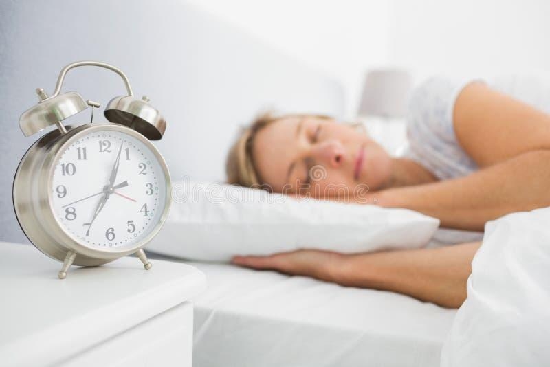 Белокурая женщина уснувшая в кровати пока ее сигнал тревоги показывает предыдущее время стоковые фото