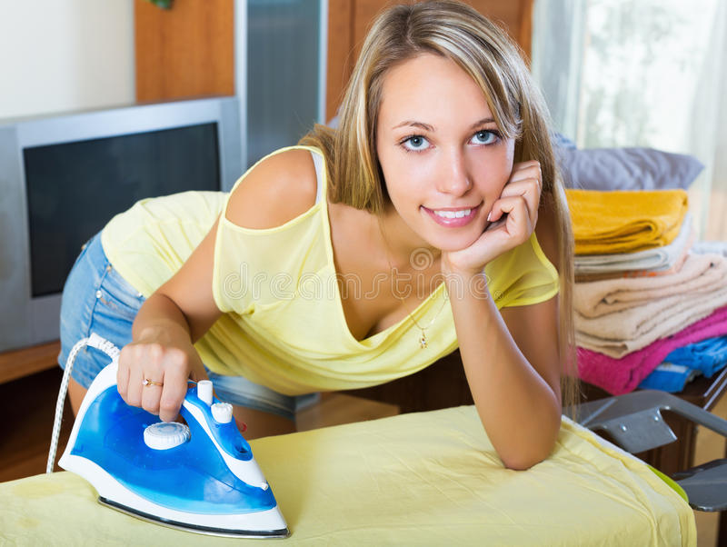 Белокурая женщина утюжа с утюгом стоковая фотография