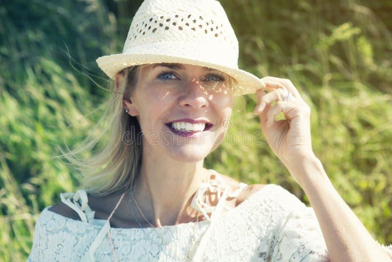 Белокурая женщина outdoors усмехаясь на камере стоковое фото rf