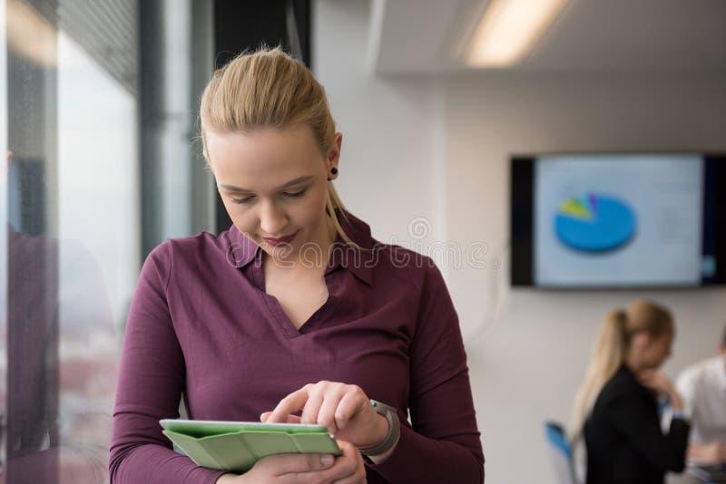 Белокурая коммерсантка работая на таблетке на офисе стоковая фотография