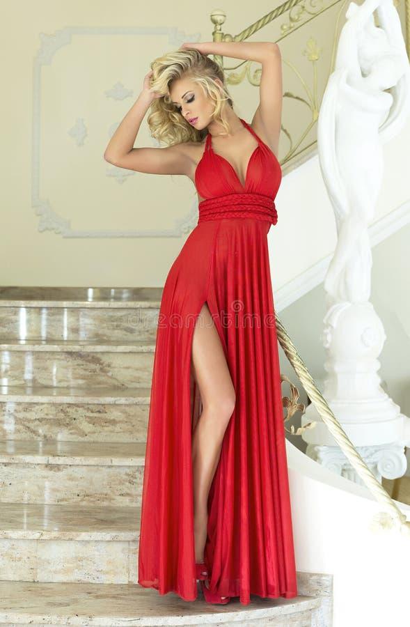 Белокурая красивая женщина представляя в красном платье. стоковое изображение rf