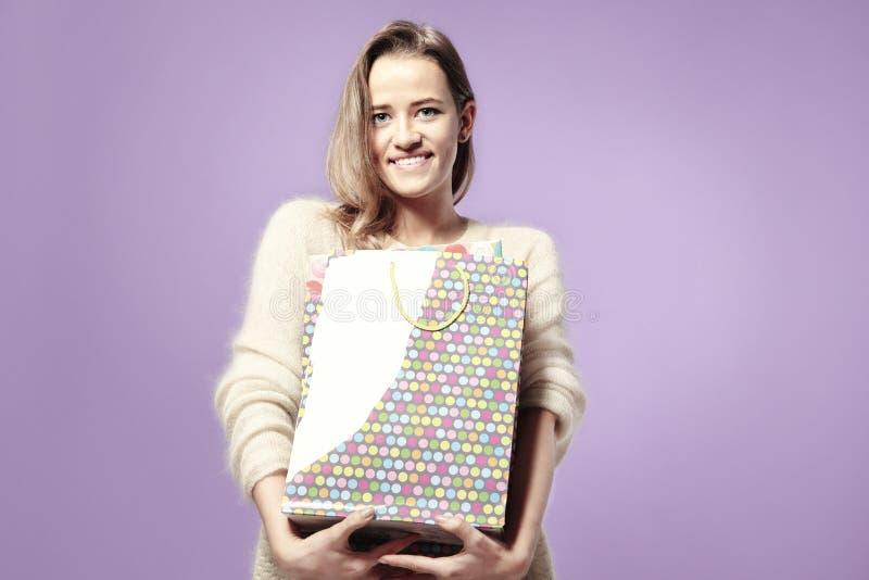 Белокурая красивая кавказская женщина счастливая с подарочной оберткой кладет в мешки в руках Нося теплый свитер, счастливые эмоц стоковая фотография rf