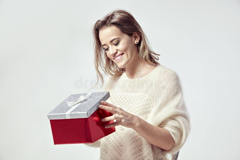Белокурая красивая кавказская женщина с присутствующей коробкой в руках Нося теплый свитер, счастливые эмоции Концепция дня вален стоковые изображения