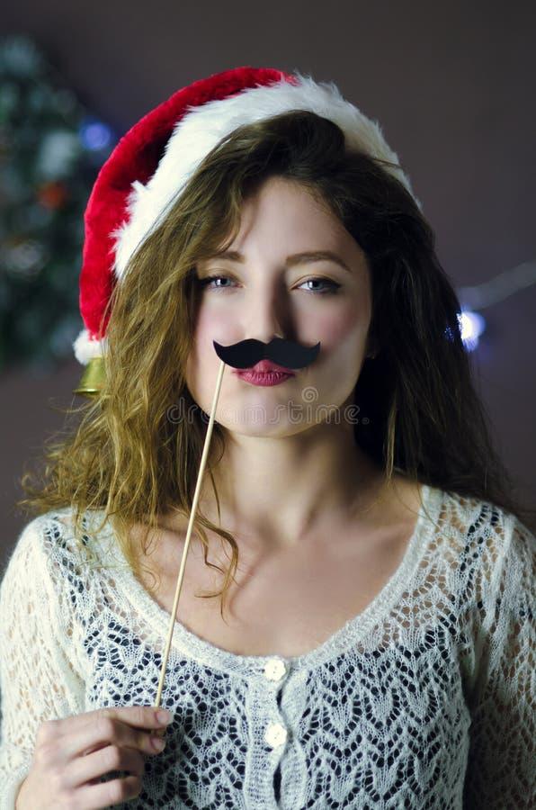 Белокурая курчавая красивая усмехаясь шляпа рождества девушки нося держа усик потехи бумажный на предпосылке украшений рождества стоковая фотография