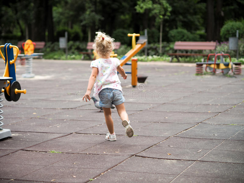 Белокурая маленькая девочка бежать в спортивной площадке стоковое изображение rf