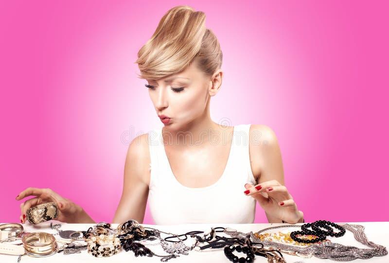 Белокурая молодая женщина выбирая ювелирные изделия стоковые изображения rf