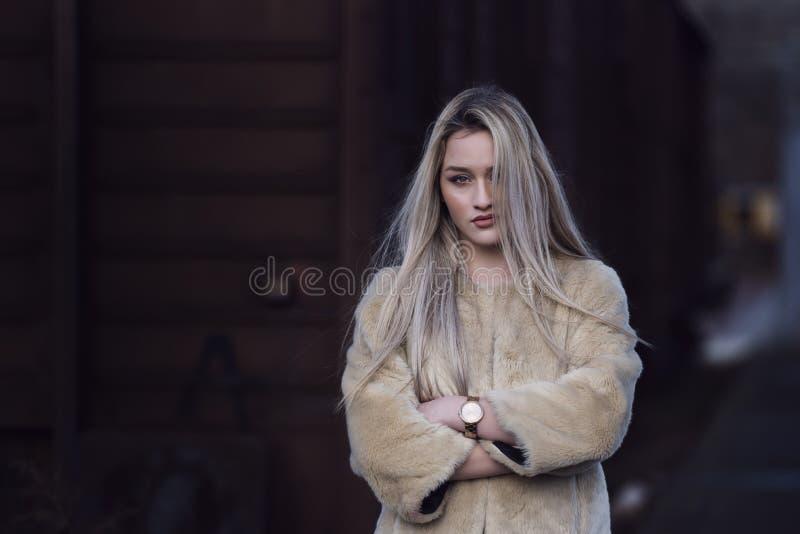 Белокурая молодая женщина против поезда фур стоковая фотография