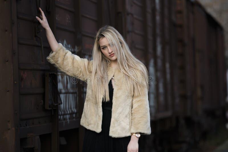 Белокурая молодая женщина против поезда фур стоковое фото rf