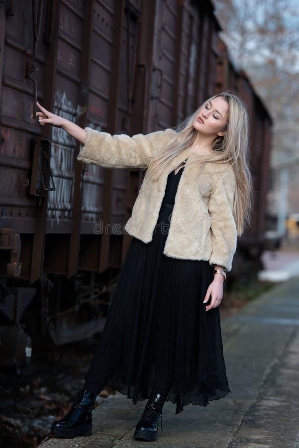 Белокурая молодая женщина против поезда фур стоковое фото