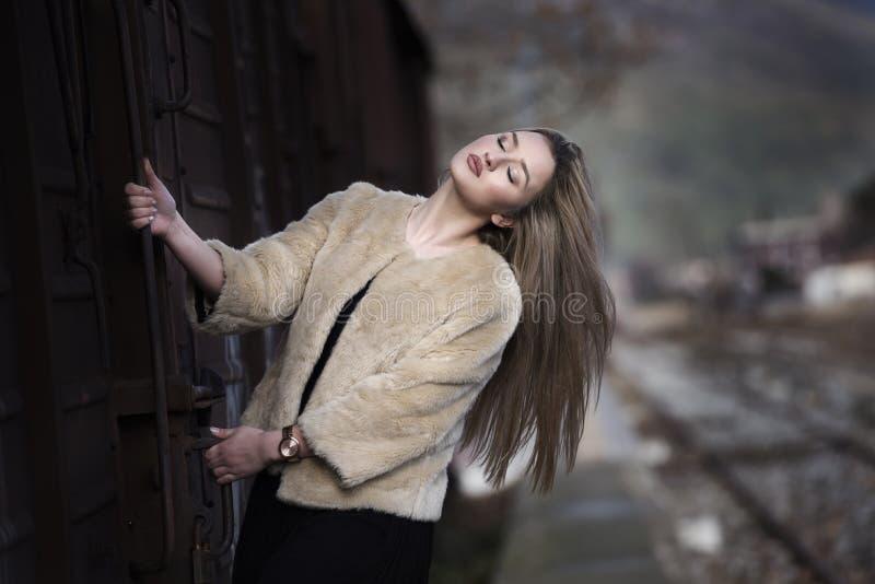Белокурая молодая женщина против поезда фур стоковое изображение rf