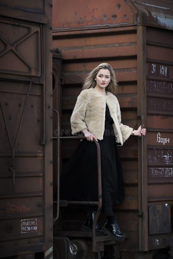 Белокурая молодая женщина среди поезда фур стоковые фотографии rf