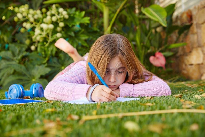 Белокурая домашняя работа девушки ребенк лежа на дерновине травы стоковое изображение