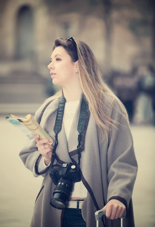 Белокурая положительная девушка держа брошюру в руках стоковые изображения