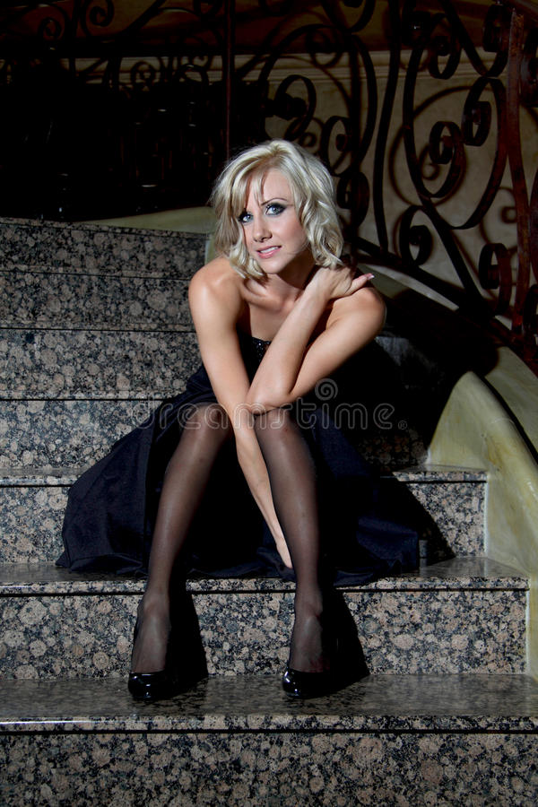 Белокурая синь наблюдала, модель очарования с черным платьем вечера стоковое изображение rf