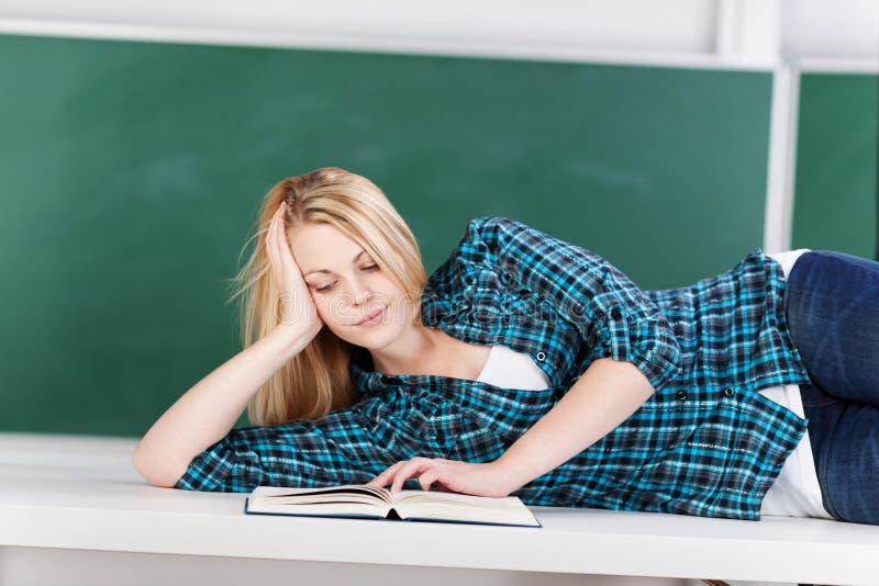 Белокурая студентка лежа на столе в классе стоковое фото