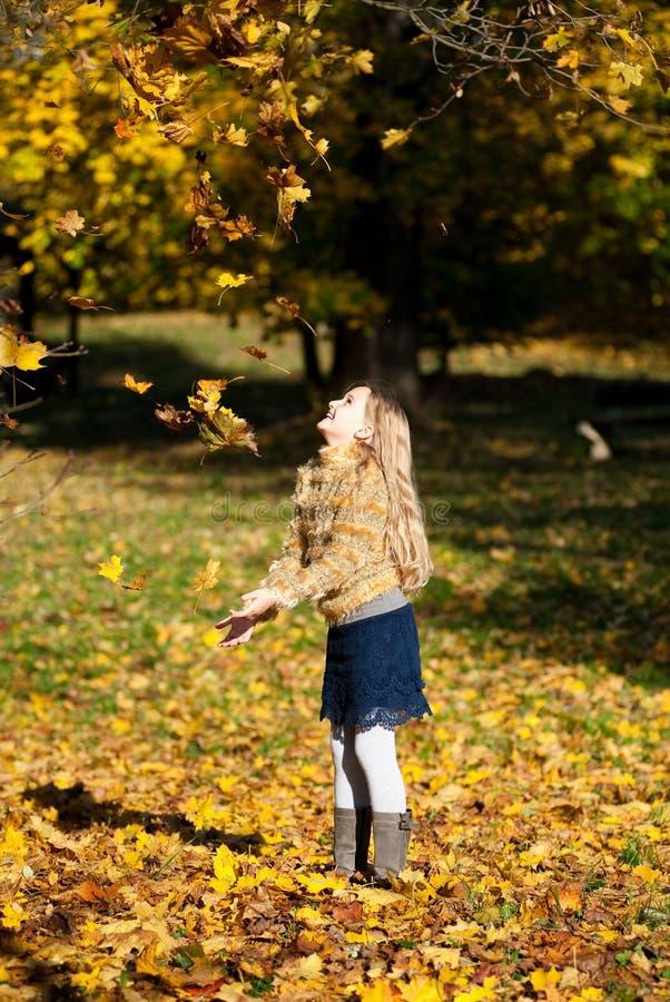 Белокурая счастливая девушка бросая вверх листья стоковое изображение rf