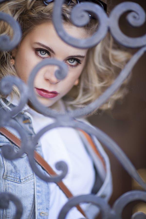 Белокурая с волосами синь наблюдала молодая женщина смотря через детальную железную дверь стоковое изображение