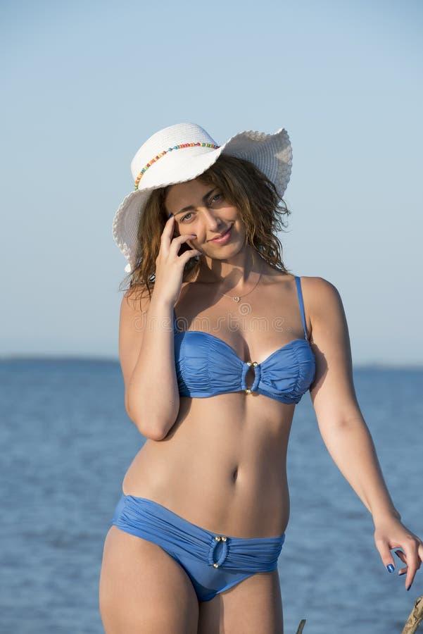 Белокурое бикини носки женщины голубое и белая шляпа стоя на море стоковые изображения rf