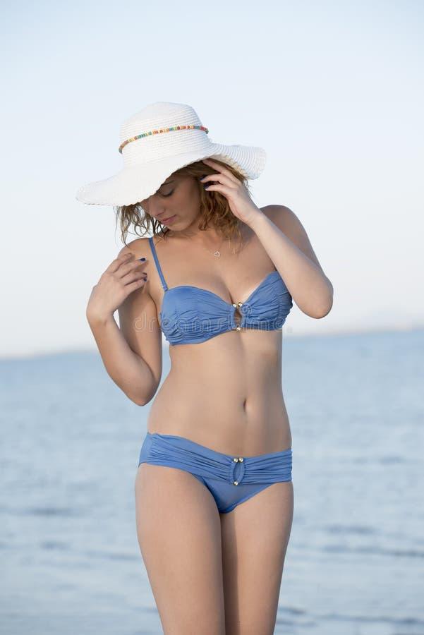 Белокурое бикини носки женщины голубое и белая шляпа стоя на море стоковая фотография