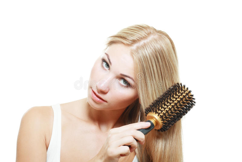 Белокурые детеныши чистя ее волосы щеткой стоковые фотографии rf