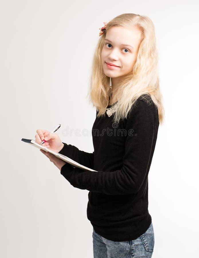 Белокурые предназначенные для подростков примечания сочинительства девушки на блокноте стоковое изображение rf