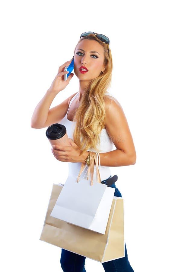 Белокурые shopaholic сумки и smartphone женщины стоковое фото rf