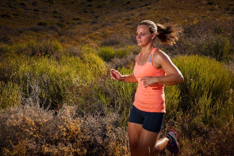 Белокурый женский бегун следа бежать через ландшафт горы стоковая фотография