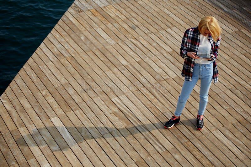 Белокурый женский турист смотря к экрану таблетки стоковые изображения rf