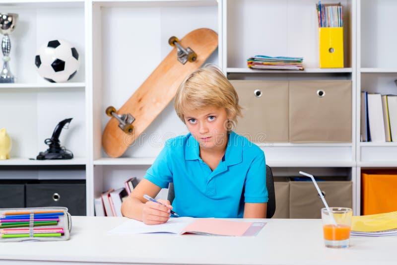 Белокурый мальчик делая домашнюю работу стоковая фотография rf