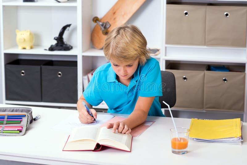 Белокурый мальчик делая домашнюю работу стоковые фотографии rf