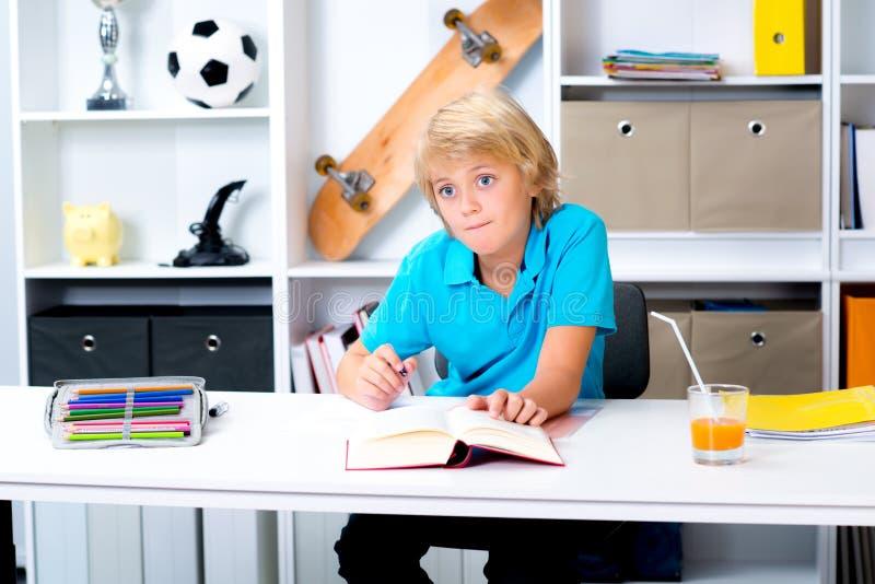 Белокурый мальчик делая домашнюю работу стоковая фотография