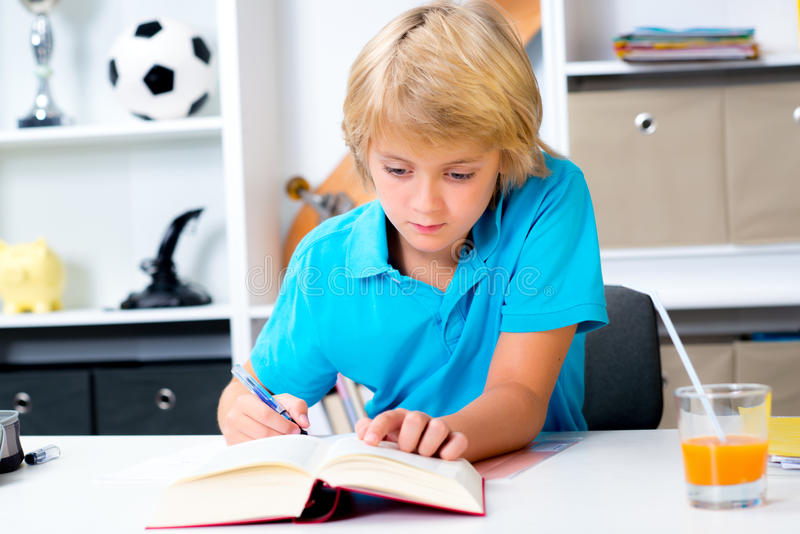 Белокурый мальчик делая домашнюю работу стоковые фото