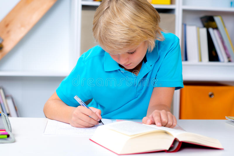 Белокурый мальчик делая домашнюю работу стоковые изображения rf