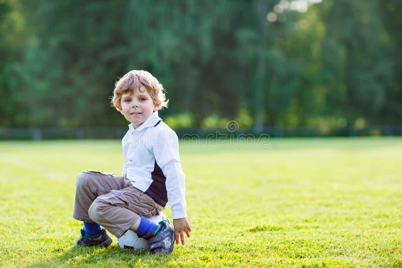 Белокурый мальчик 4 отдыхая с футболом на футбольном поле стоковые изображения