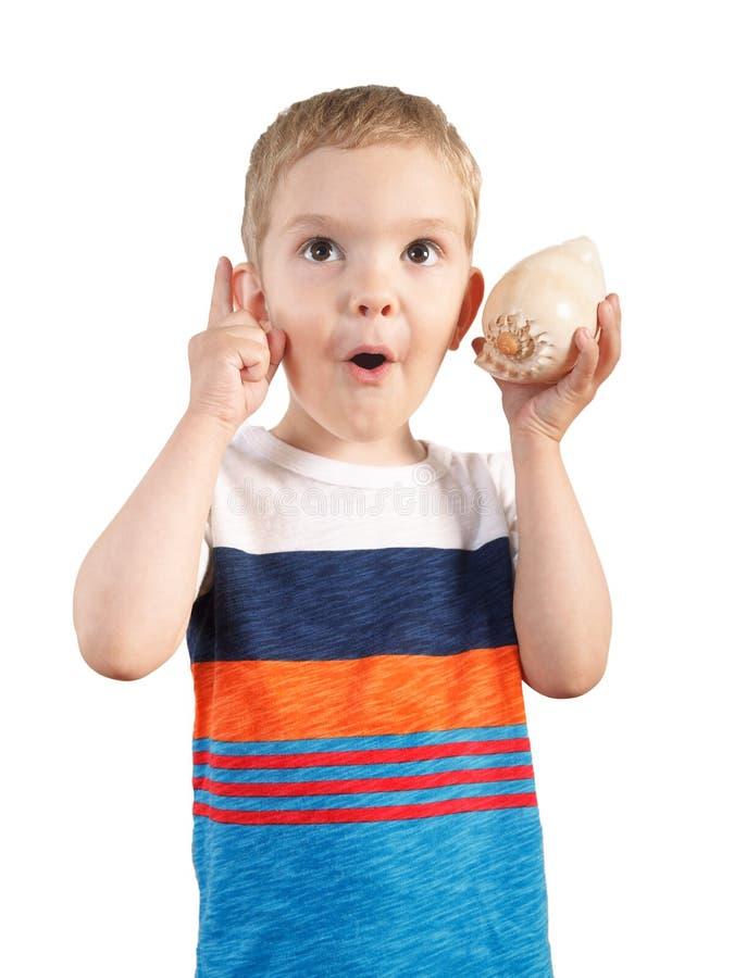 Белокурый мальчик слушая к seashell Изолировано на белизне стоковое фото