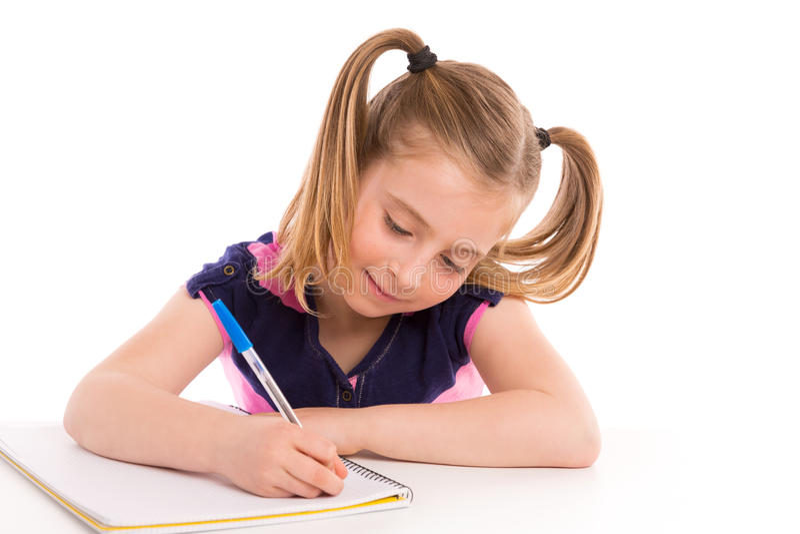 Белокурый студент девушки ребенк с спиральной тетрадью в столе стоковое фото