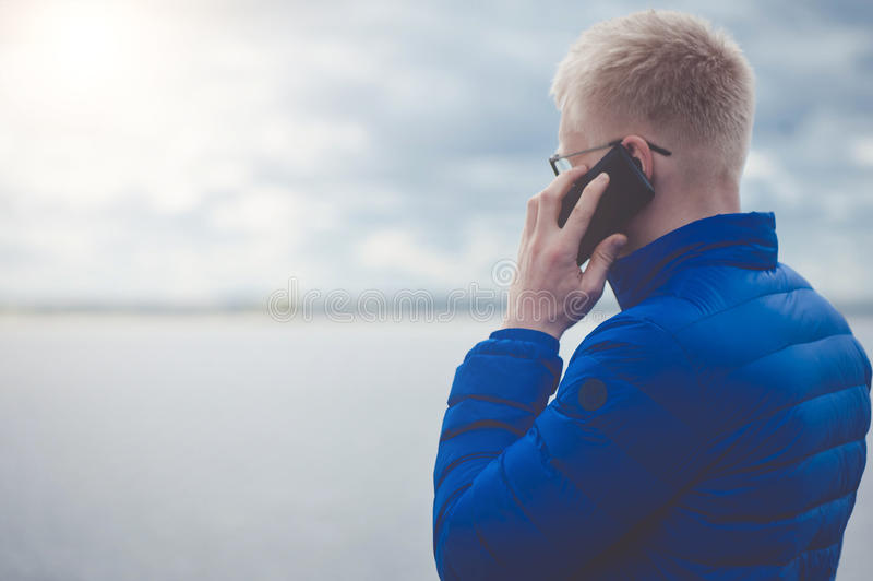 Белокурый человек используя мобильный телефон на озере стоковая фотография