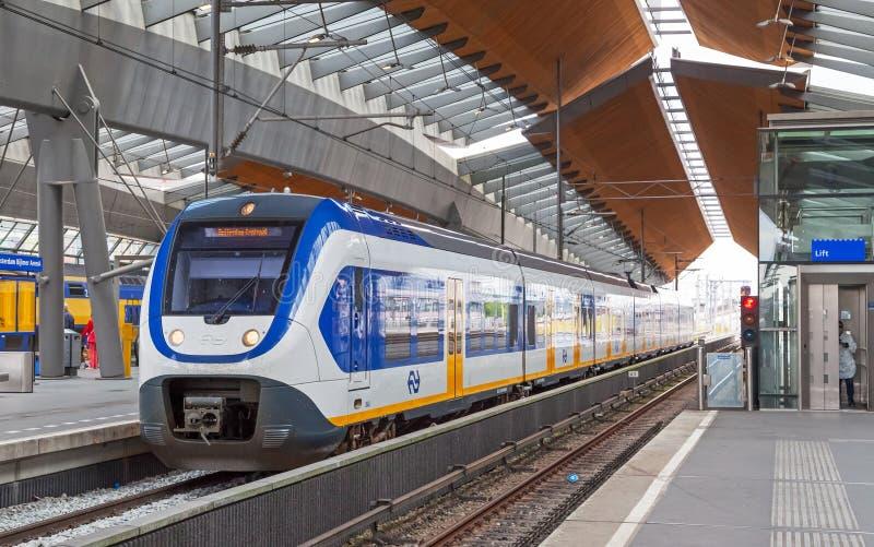 Бело-голубой поезд остается на станции арены Амстердама стоковая фотография