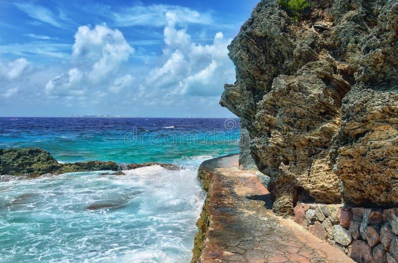 Белые волны голубого моря ломая на утесах стоковые изображения rf