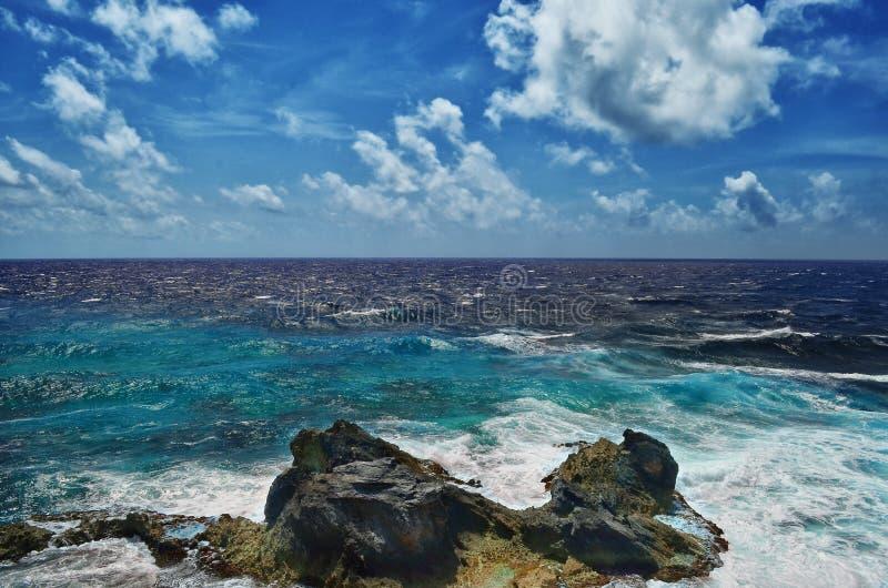 Белые волны голубого моря ломая на утесах стоковое фото rf