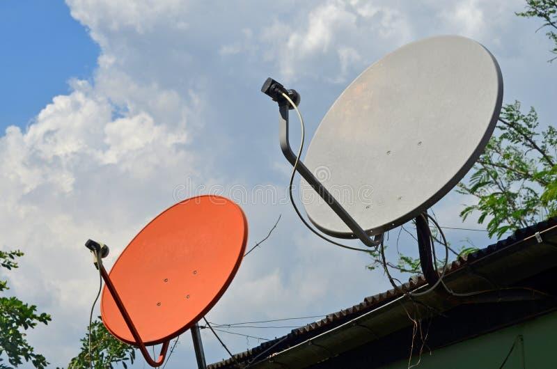 Белые и красные спутниковые антенна-тарелки стоковое фото rf