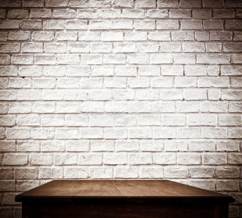 Белые кирпичная стена и деревянный стол стоковое изображение rf