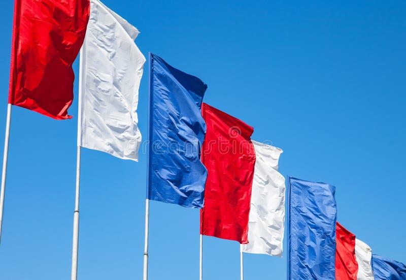 Белые, красные и голубые флаги развевая на предпосылке неба стоковая фотография rf